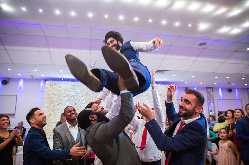 men dancing and throwing groom up in the air on the dancefloor