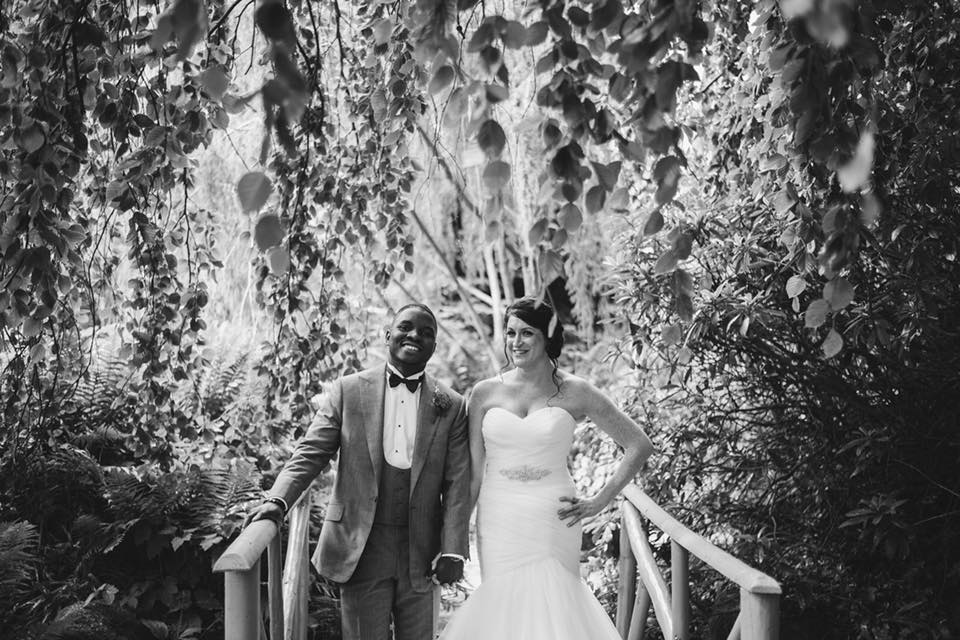 black and white photo of multicultural wedding couple on a bridge smiling