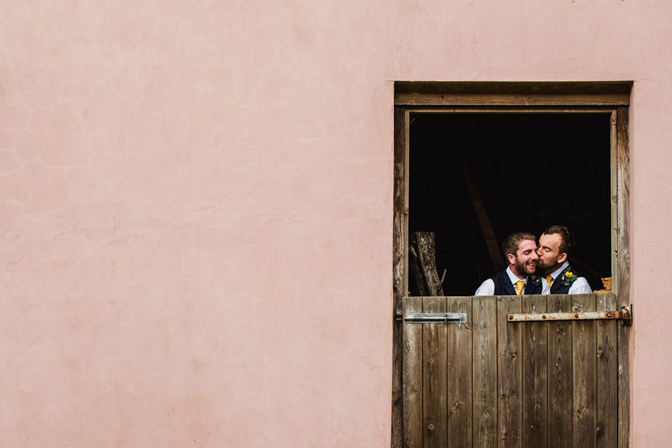 two men kissing on their wedding day in a barn