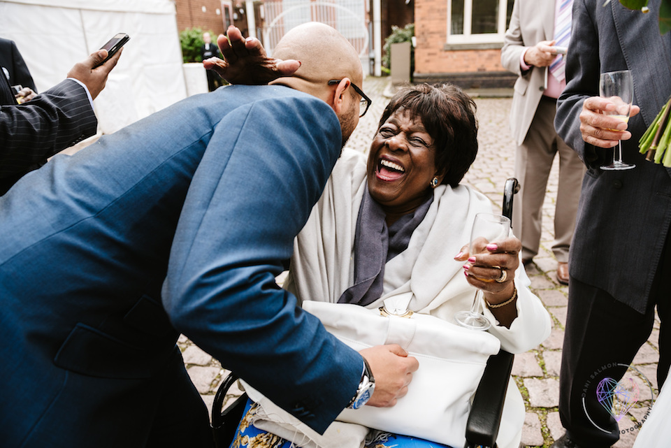 elderly relative in a wheelchair joyfully hugging man in navy suit at wedding