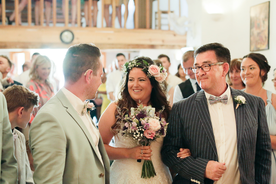 smiling bride walking down aisle with father on her arm, with groom looking at her with hearing aid