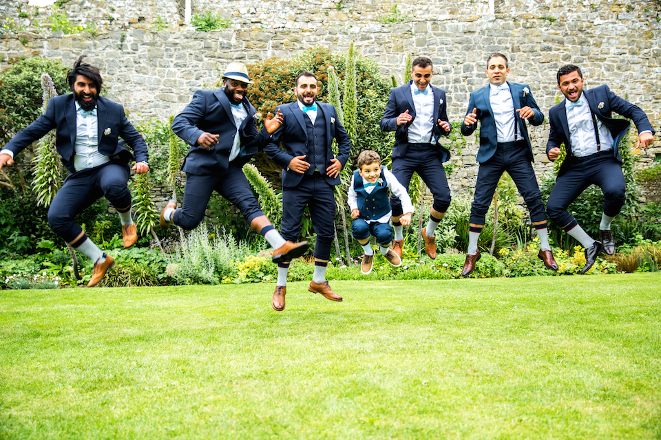 Men and small boy jumping for joy at wedding in the grass wearing navy blue suits, bow ties and brown shoes