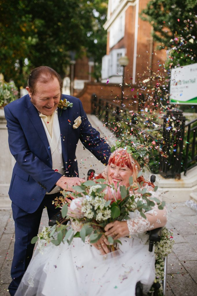 smiling mature bride with red and blonde hair in a wheelchair showered in confetti with her smiling groom