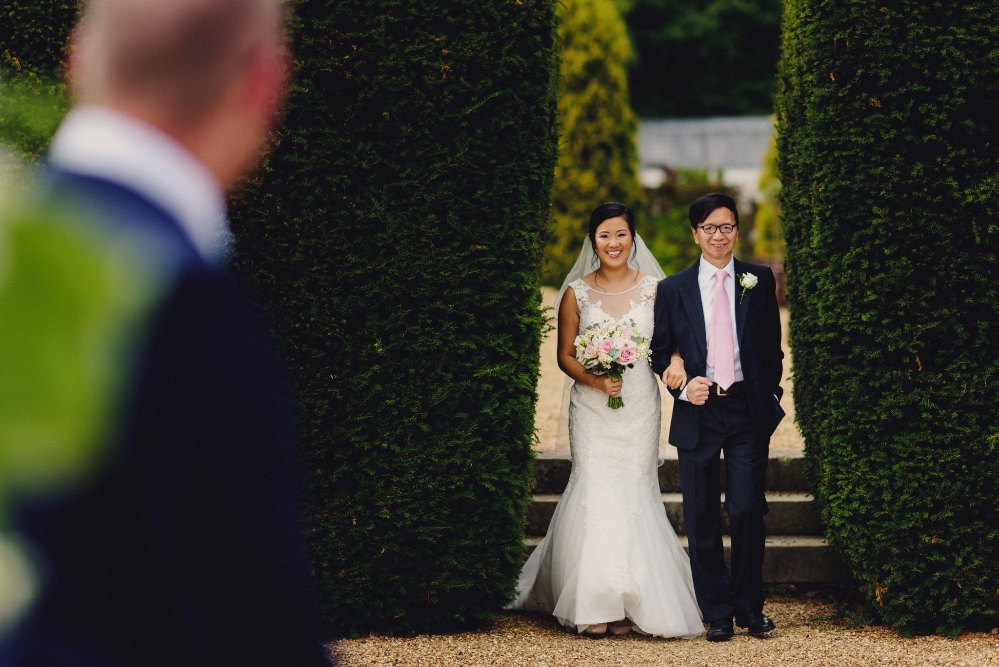 Bride walking up aisle Fun Elegant British Chinese Wedding at Hartsfield Manor