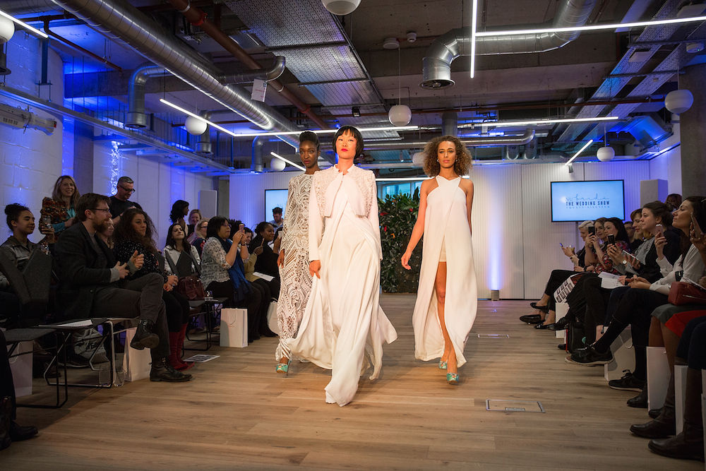 Three diverse women modeling unique white wedding gowns at a London wedding industry show
