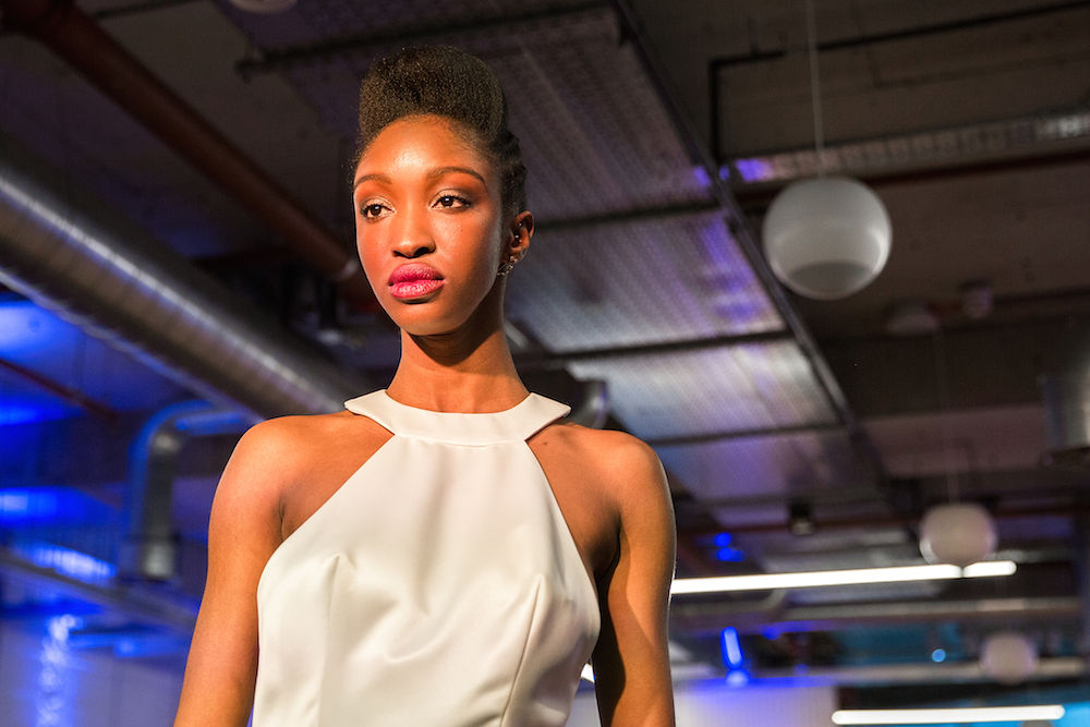 Black woman modeling an elegant white wedding dress at a wedding industry show in London UK