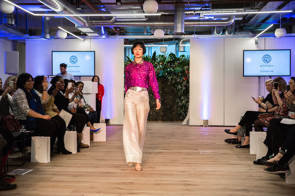 A woman of color modeling a bright magenta blouse and white pants at a London wedding industry event
