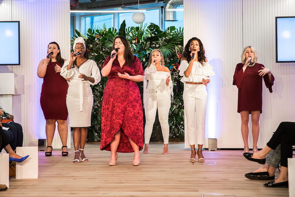 A driver group of six women singing at a wedding industry event in London UK