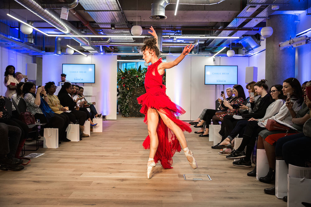 Professional dancer in a red dress and ballet shoes dancing for a crowd in London UK