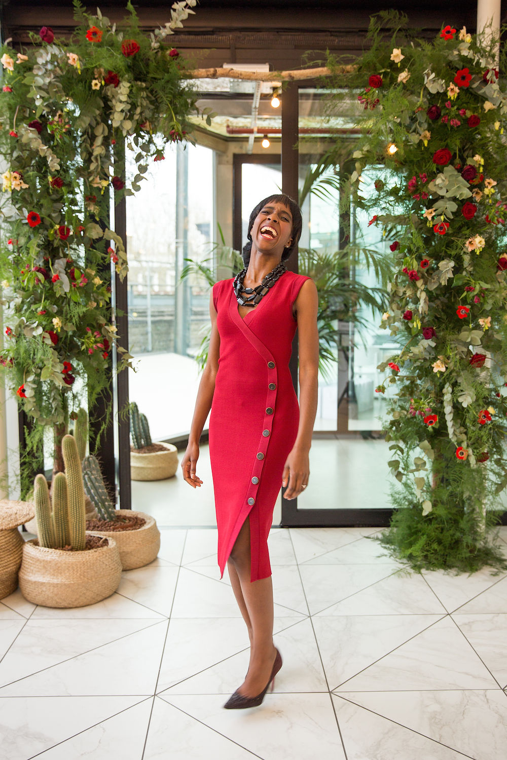 A black woman in a red dress laughing happily before large floral decorations in London UK