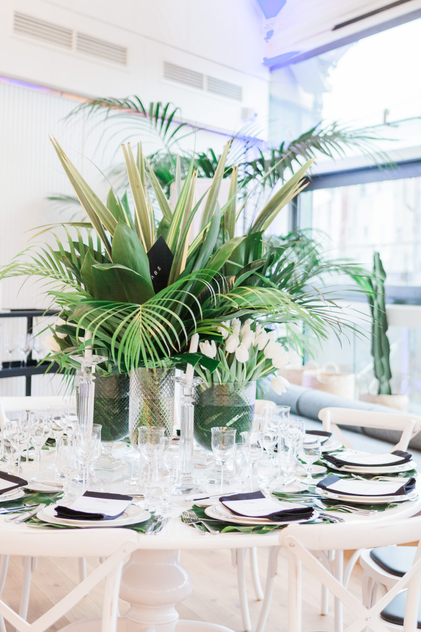 Unique tropical greenery center piece on a table set for a wedding reception in London