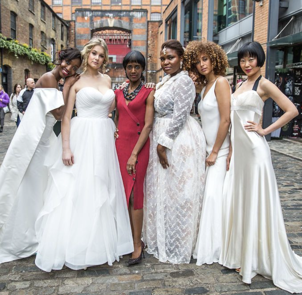 Elegant diverse models in white wedding gowns posing with the black designer in a London street